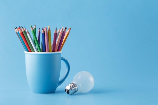 Kreatives ideenkonzept der kunst, stifte im becher und in der glühbirne
