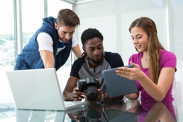 Kreatives junges geschäftsteam, das digitale tablette betrachtet