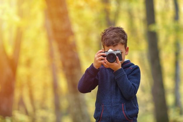 Kreatives kind, kinderfotograf (ein kleiner junge) mit einer kamera, die bilder des bunten herbstwaldes macht