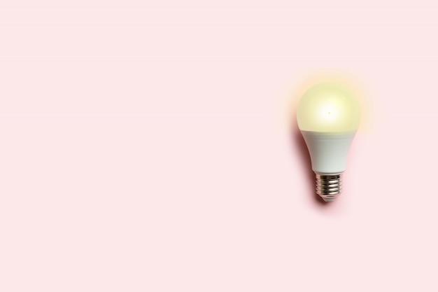 Kreatives konzept einer leuchtenden energiesparenden glühlampe auf einem rosa hintergrund. energieeinsparung oder idee