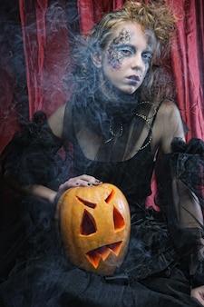 Kreatives konzept. halloween-hexe mit geschnitztem kürbis über rotem hintergrund.