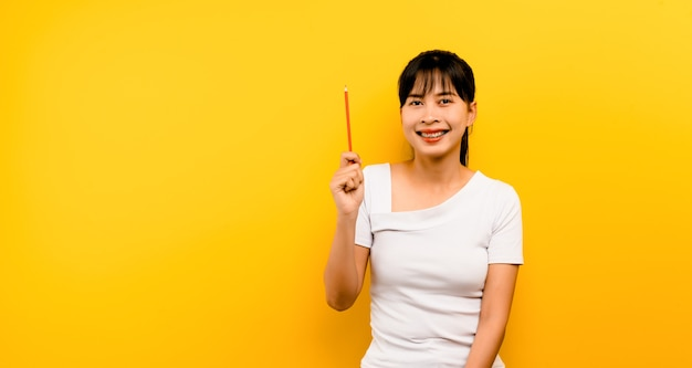 Kreatives konzept nahaufnahme einer asiatischen frau erstaunliche frau, die freien raum sucht, tief denkend, kreativ und mit einem glücklichen lächeln auf gelbem hintergrund
