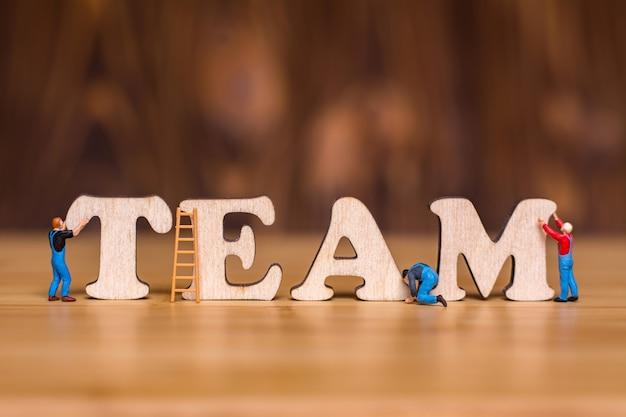 Kreatives konzept zur teamarbeit. miniaturmenschen und holzbuchstaben team. zahlen von arbeitern.