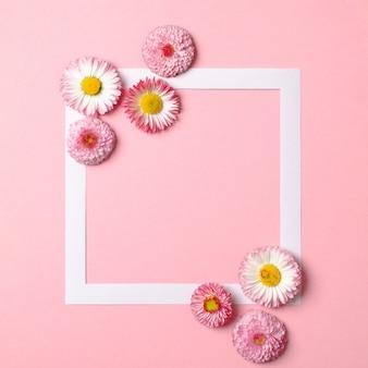 Kreatives layout aus bunten frühlingsblumen und papierrandrahmen auf pastellrosa hintergrund. minimales urlaubskonzept.