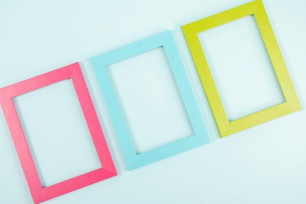 Kreatives layout aus drei bunten rahmen auf blauem hintergrund. flat lay draufsicht kopierraum mockup.