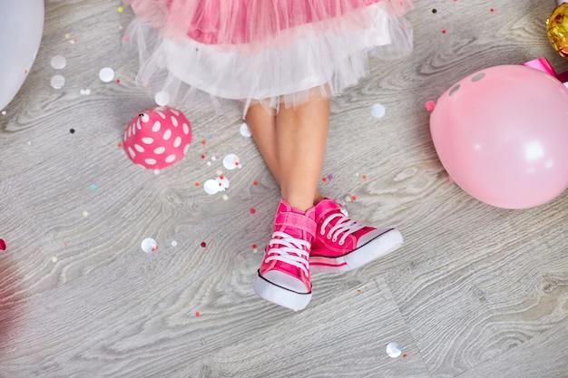 Kreatives layout aus funky bein des mädchens in rosa turnschuhen und kleid, flach