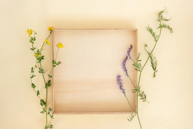 Kreatives layout aus holzkiste und wilden blumen und blättern mit papierkartennotiz.