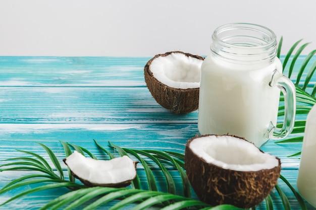 Kreatives layout aus kokosnüssen und tropischen blättern. food-konzept