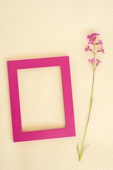Kreatives layout aus lila rahmen und wilder blume auf papierkartennotiz.