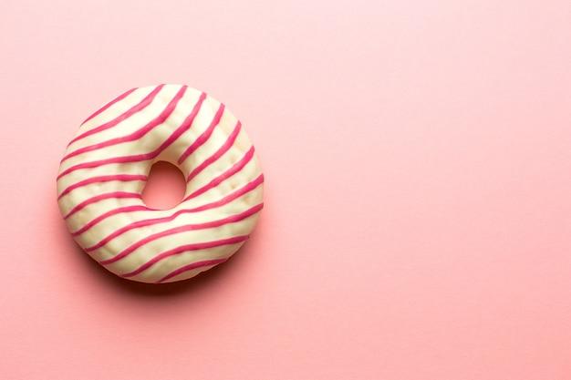Kreatives layout aus pink glasierten donuts. flach liegen. lebensmittelkonzept. makrokonzept. verschiedene verzierte donuts auf weichem rosa hintergrund. süße und bunte donuts