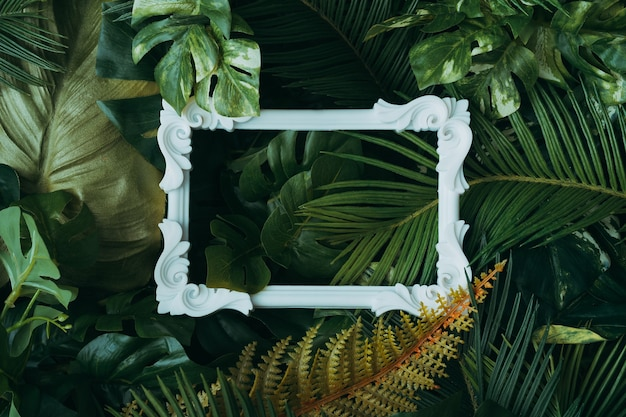 Kreatives layout aus tropischen blättern mit vintage-rahmen. naturkonzept.