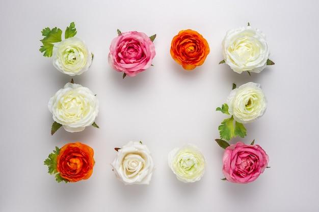 Kreatives layout der schönen rosenblumen auf weißer oberfläche.