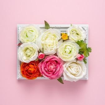 Kreatives layout der schönen rosenblumen im rahmen auf rosa oberfläche.