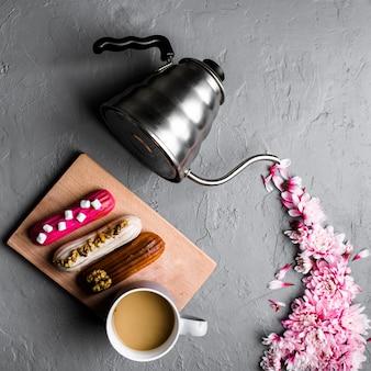 Kreatives layout der teekanne mit chrysanthemenblumen auf grauem betontisch