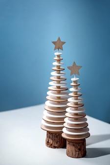 Kreatives layout des weihnachtsgrußdesigns des neuen jahres mit modernen hölzernen tannenbäumen der weihnachtsdekoration und kreativen aquarellelementen über blau