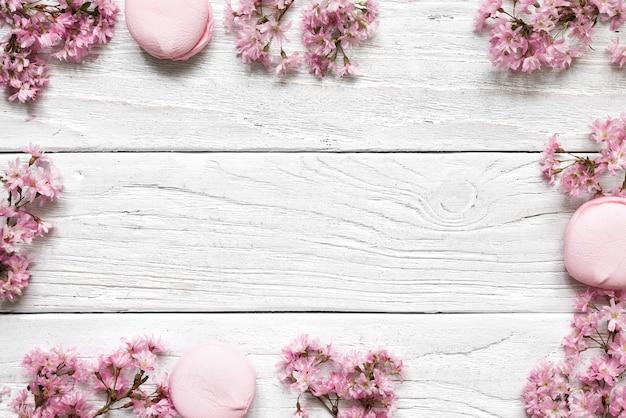 Kreatives layout gemacht mit rosa kirschblütenblumen auf weißem hölzernem hintergrund. flach liegen. draufsicht. hochzeitsrahmen