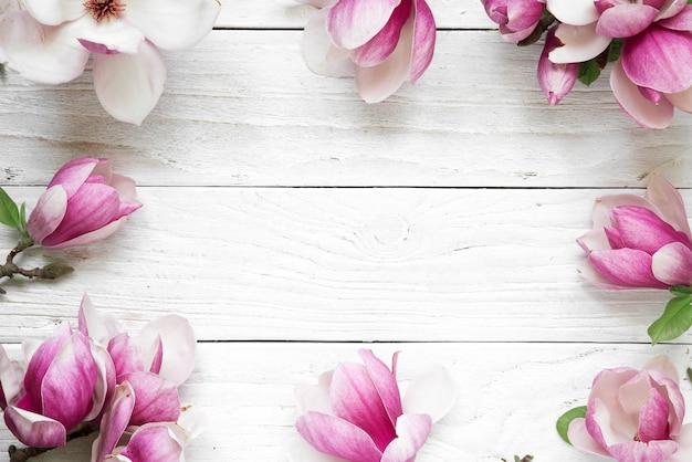 Kreatives layout gemacht mit rosa magnolienblumen auf weißem hölzernem hintergrund. flach liegen. draufsicht