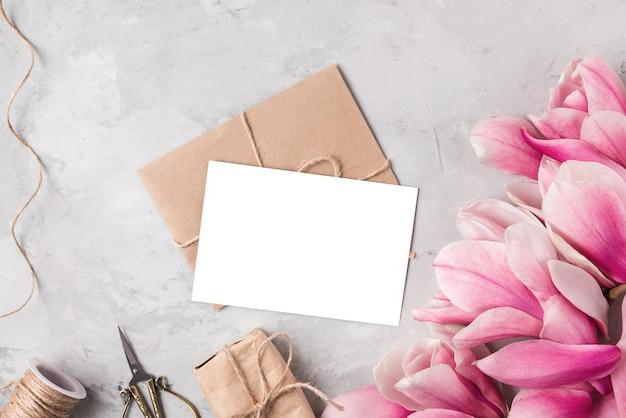 Kreatives layout gemacht mit rosa magnolienblumen, grußkarte, geschenkbox und seil auf grauem tisch. flach liegen.