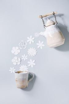 Kreatives layout mit einer vielzahl von weißen papierblumen, die von der keramik-teekanne zur tasse über der grauen wand fließen. flache lage, kopierraum. blumentee, sommer- oder frühlingszeitkonzept