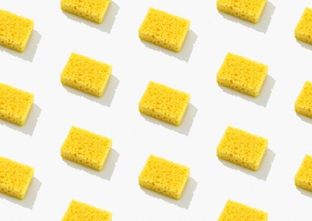 Kreatives layout mit gelbem schwamm zum geschirrspülen auf grauem hintergrund. reinigungsservicekonzept