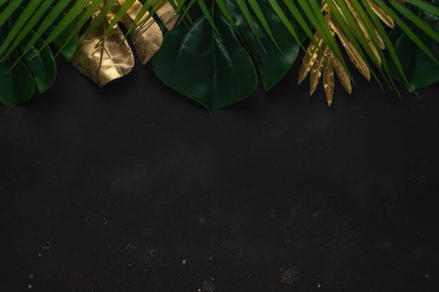 Kreatives layout mit goldenen und grünen tropischen palmblättern auf schwarzem hintergrund