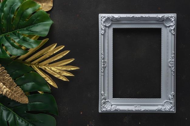 Kreatives layout mit goldenen und grünen tropischen palmblättern mit weißem rahmen auf schwarzem hintergrund