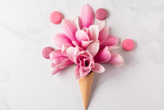 Kreatives layout mit rosa magnolienblüten im waffelkegel mit makronen. flach liegen