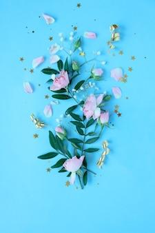 Kreatives layout mit rosa und violetten blumen auf blauem hintergrund. flach liegen. frühling minimales konzept.