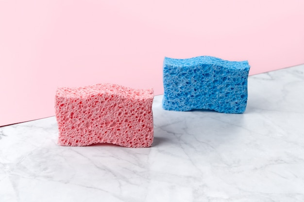 Kreatives layout mit schwämmen zum geschirrspülen auf rosa und marmor-doppelhintergrund. reinigungsservice-vorlage