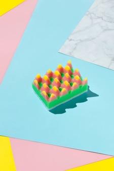 Kreatives layout mit schwamm zum geschirrspülen auf mehrfarbigem hintergrund. reinigungsservicekonzept