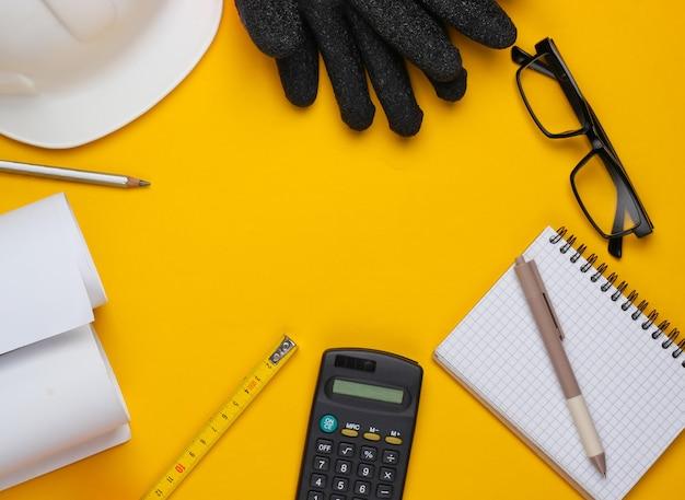 Kreatives layout von architekten mit rollenzeichnungen, architektonischem projektplan, technischen werkzeugen und briefpapier auf gelbem hintergrund, arbeitsbereich. draufsicht. flach liegen. speicherplatz kopieren