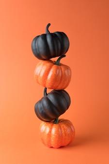 Kreatives layout von schwarzen und herbstkürbissen mit orange hintergrund
