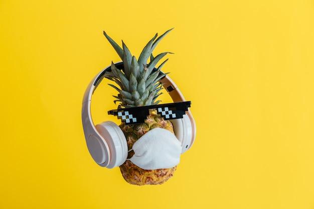 Kreatives lustiges ananasgesicht mit brillenkopfhörern und medizinischer schutzmaske. schwebendes ananasgesicht auf gelbem sommerhintergrund ruhen. coronavirus-reisekonzept.