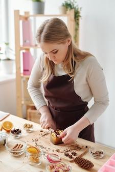 Kreatives mädchen mit messer, das handgemachte seifenstück mit aromatischen gewürzen und orangenscheiben auf holzbrett durch tisch schneidet