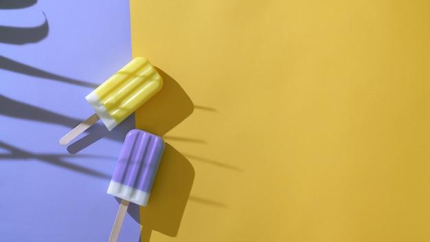Kreatives minimales sommerkonzept, draufsicht von zwei bunten eis am stiel auf lila und gelbem hintergrund
