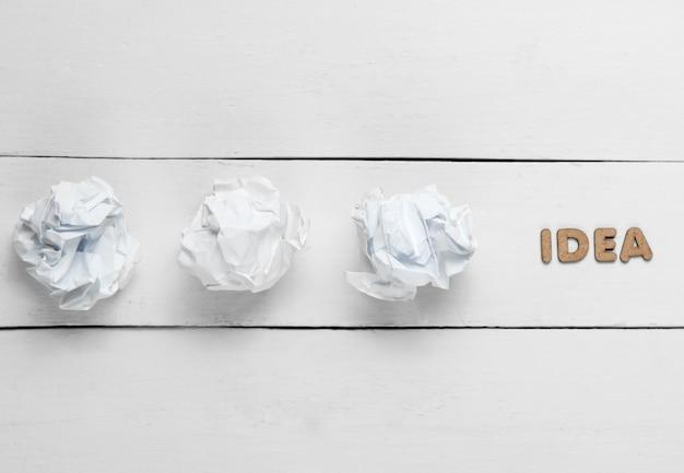 Kreatives minimalistisches konzept. zerknitterte papierkugeln auf weißem holz mit wortidee