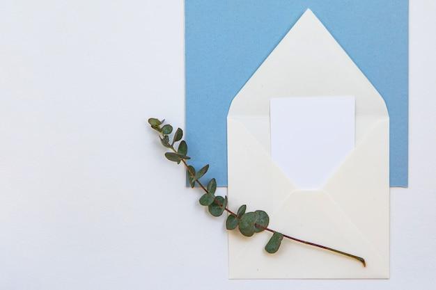 Kreatives modelllayout mit papierkarte für beschriftungsnotiz, weißem umschlag und grünem zweig. flaches laienhochzeits- oder valentinstag-minimalkonzept.