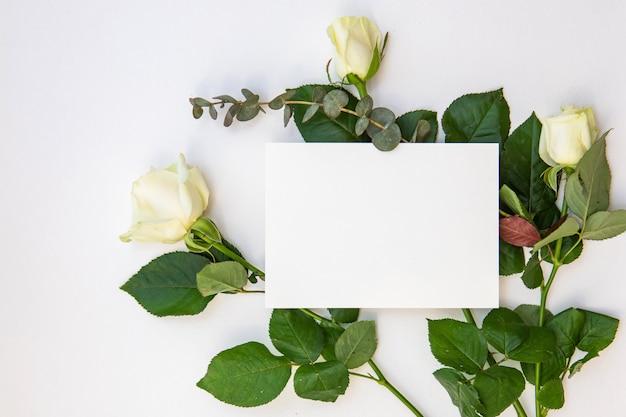 Kreatives modelllayout mit papierkarte für inschriften und rosenblüten. flaches laienhochzeits- oder valentinstag-minimalkonzept.