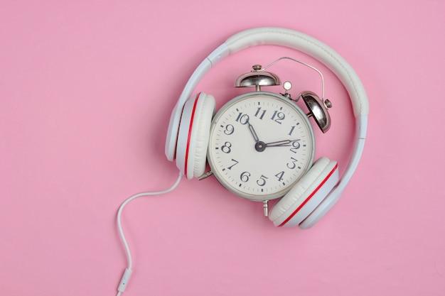 Kreatives musikkonzept. retro wecker und klassische kopfhörer auf rosa hintergrund. popkultur. 80er jahre.