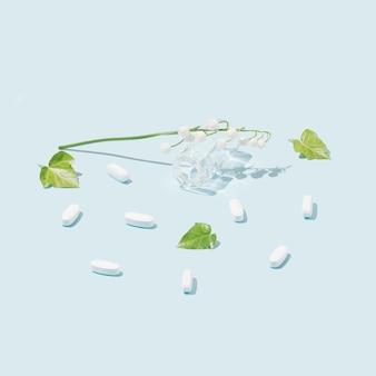 Kreatives muster aus weißen drogentabletten auf pastellblauem hintergrund und grünen blättern.