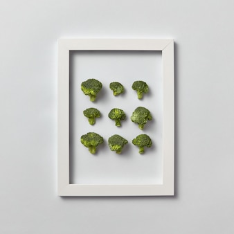 Kreatives muster des natürlichen frisch gepflückten bio-brokkolis in einem rahmen auf einer hellgrauen wand, platz für text. draufsicht. vegetarisches lebensmittelkonzept.