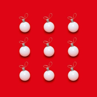Kreatives muster mit weißen neujahrskugeln, feiertagsspielzeug auf leuchtendem rot
