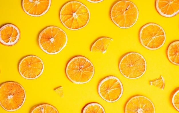 Kreatives muster von getrockneten orange scheiben. geometrisches muster von orange scheiben auf farbe