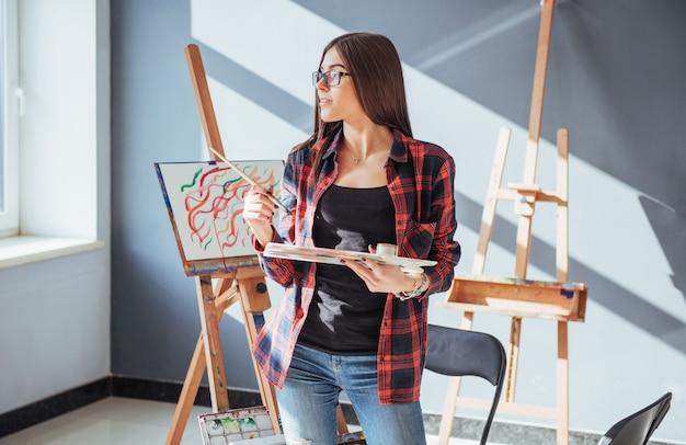 Kreatives nachdenkliches malermädchen malt ein buntes bild auf segeltuch mit ölfarben in der werkstatt.