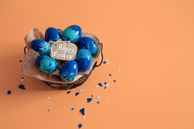 Kreatives osterlayout aus bunten eiern und blumen auf blau.