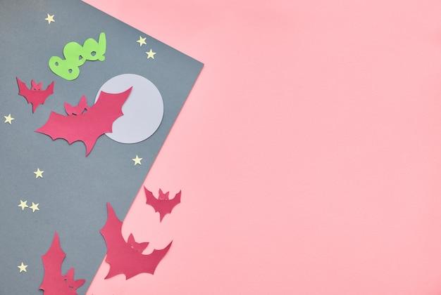 Kreatives papierhandwerk halloween flach lag auf geteiltem papierhintergrund in den rosa und grauen pastellfarben