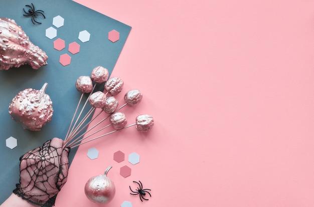 Kreatives papierhandwerk halloween flach lag auf rosa und grauer geteilter papierwand mit schokoladenaugen und spinnen, kopierraum. hände in schwarzen netzhandschuhen, die gemalte äpfel halten