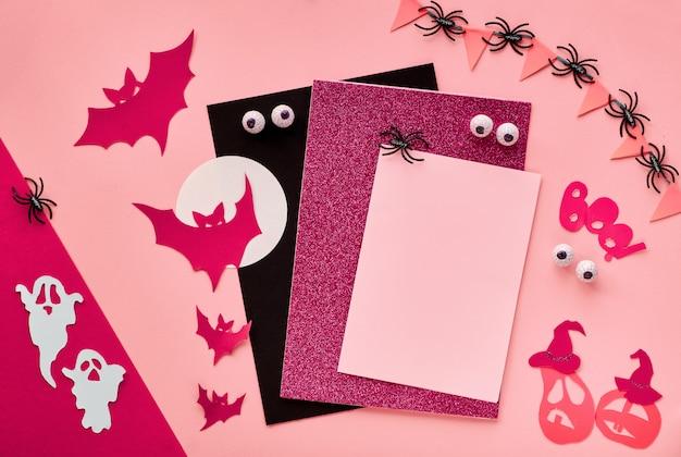 Kreatives papierhandwerk halloween flach lag hintergrund in dunkelrot. kopierfläche auf leeren karten, fledermäusen, geistern, schokoladenaugen, kürbissen und dem wort