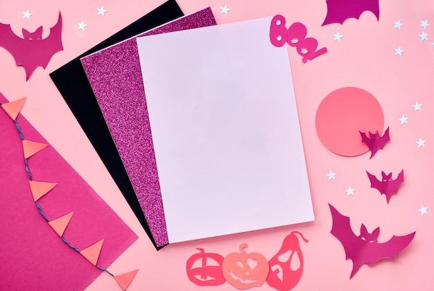 Kreatives papierhandwerk halloween flach lag in rosa, magenta und schwarz. draufsicht mit cipy-raum auf kartenstapel, fledermäusen, schokoladenaugen, kürbissen und und wort