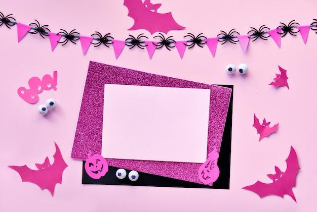 Kreatives papierhandwerk halloween flach lag in rosa und schwarz. draufsicht mit cipy-raum auf papierkarten, fledermäusen, schokoladenaugen, kürbislaternenkürbissen, flagge von flaggen und spinnen.